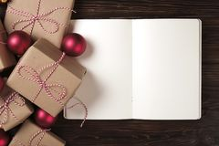 Σημειωματάριο με τη διακόσμηση Χριστουγέννων και δώρα στο ξύλινο υπόβαθρο Για να κάνει τον κατάλογο, έννοια επιστολών santa Η τοπ Στοκ εικόνα με δικαίωμα ελεύθερης χρήσης