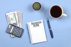 Σημειωματάριο με τη μάνδρα, τον καφέ, τα δολάρια, τον υπολογιστή και τον κάκτο σε ένα μπλε υπόβαθρο Αντιγράψτε το διάστημα Τοπ όψ Στοκ εικόνα με δικαίωμα ελεύθερης χρήσης