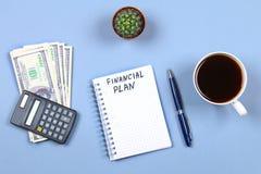 Σημειωματάριο με τη μάνδρα, τον καφέ, τα δολάρια, τον υπολογιστή και τον κάκτο σε ένα μπλε υπόβαθρο Αντιγράψτε το διάστημα Τοπ όψ Στοκ Εικόνες