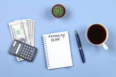 Σημειωματάριο με τη μάνδρα, τον καφέ, τα δολάρια, τον υπολογιστή και τον κάκτο σε ένα μπλε υπόβαθρο Αντιγράψτε το διάστημα Τοπ όψ Στοκ Φωτογραφίες