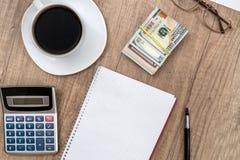 Σημειωματάριο με τη μάνδρα, τον υπολογιστή, τον καφέ και το δολάριο Στοκ εικόνα με δικαίωμα ελεύθερης χρήσης