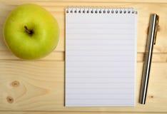 Σημειωματάριο με τη μάνδρα πηγών και τα φρούτα μήλων Στοκ εικόνα με δικαίωμα ελεύθερης χρήσης