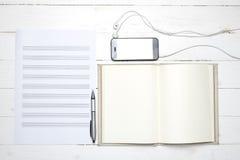Σημειωματάριο με τη σημείωση εγγράφου μουσικής και το έξυπνο τηλέφωνο Στοκ Φωτογραφία