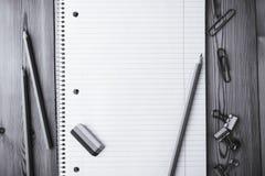 Σημειωματάριο με τους συνδετήρες εγγράφου, μολύβι, γόμα σε ένα ξύλινο υπόβαθρο στοκ εικόνες