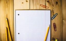 Σημειωματάριο με τους συνδετήρες εγγράφου, μολύβι, γόμα σε ένα ξύλινο υπόβαθρο στοκ φωτογραφία