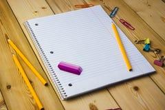 Σημειωματάριο με τους συνδετήρες εγγράφου, μολύβι, γόμα σε ένα ξύλινο υπόβαθρο στοκ εικόνα