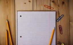Σημειωματάριο με τους συνδετήρες εγγράφου, μολύβι, γόμα σε ένα ξύλινο υπόβαθρο στοκ φωτογραφία με δικαίωμα ελεύθερης χρήσης