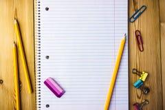 Σημειωματάριο με τους συνδετήρες εγγράφου, μολύβι, γόμα σε ένα ξύλινο υπόβαθρο στοκ φωτογραφίες με δικαίωμα ελεύθερης χρήσης