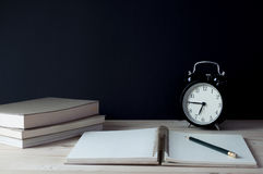 Σημειωματάριο με το ρολόι μολυβιών και βιβλία στον πίνακα Στοκ Εικόνες
