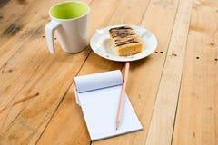 Σημειωματάριο με το φλυτζάνι και το κέικ καφέ στοκ εικόνα με δικαίωμα ελεύθερης χρήσης