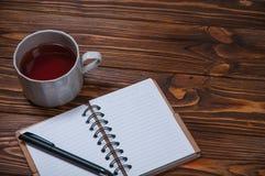Σημειωματάριο σε έναν πίνακα με μια κούπα και ένα φλυτζάνι του τσαγιού Στοκ Φωτογραφία