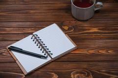Σημειωματάριο σε έναν πίνακα με μια κούπα και ένα φλυτζάνι του τσαγιού Στοκ φωτογραφία με δικαίωμα ελεύθερης χρήσης