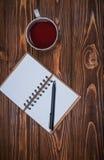 Σημειωματάριο σε έναν πίνακα με μια κούπα και ένα φλυτζάνι του τσαγιού Στοκ Εικόνα