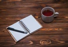 Σημειωματάριο σε έναν πίνακα με μια κούπα και ένα φλυτζάνι του τσαγιού Στοκ εικόνα με δικαίωμα ελεύθερης χρήσης