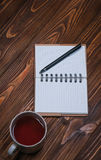 Σημειωματάριο σε έναν πίνακα με μια κούπα και ένα φλυτζάνι του τσαγιού Στοκ εικόνες με δικαίωμα ελεύθερης χρήσης