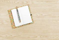 Σημειωματάριο σε μια ξύλινη ανασκόπηση Στοκ εικόνες με δικαίωμα ελεύθερης χρήσης
