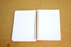 Σημειωματάριο στην ξύλινη ανασκόπηση Στοκ εικόνες με δικαίωμα ελεύθερης χρήσης