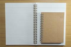 Σημειωματάριο στον ξύλινο πίνακα Τοπ όψη Στοκ Εικόνες