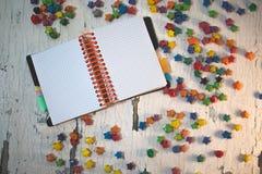 Σημειωματάριο στο άσπρο ξύλινο υπόβαθρο με τα πολύχρωμα αστέρια εγγράφου Στοκ εικόνα με δικαίωμα ελεύθερης χρήσης
