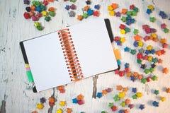 Σημειωματάριο στο άσπρο ξύλινο υπόβαθρο με τα πολύχρωμα αστέρια εγγράφου Στοκ Εικόνα