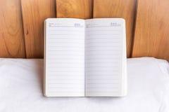 Σημειωματάριο στο ξύλινο υπόβαθρο χρησιμοποίηση της ταπετσαρίας για την εκπαίδευση, επιχειρησιακή φωτογραφία Σημειώστε το προϊόν  στοκ εικόνα με δικαίωμα ελεύθερης χρήσης