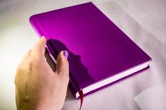 Σημειωματάριο του ιώδους χρώματος στο γραφείο Εδώ κοντά το χέρι βρίσκεται Το βιβλίο για τις σημειώσεις Άσπρη ανασκόπηση στοκ φωτογραφία με δικαίωμα ελεύθερης χρήσης