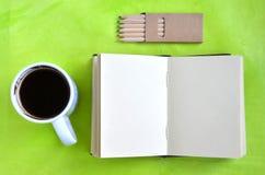 Σημειωματάριο, φλιτζάνι του καφέ και κραγιόνια στο πράσινο υπόβαθρο στοκ εικόνα με δικαίωμα ελεύθερης χρήσης