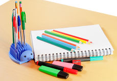 Σημειωματάριο, χρωματισμένες μολύβια και προμήθειες γραφείων Στοκ εικόνα με δικαίωμα ελεύθερης χρήσης
