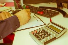 σημειώσεις γραψίματος ατόμων από τον υπολογιστή στον ξύλινο πίνακα Χέρι ατόμων με τη μάνδρα, τον υπολογιστή και τον υπολογιστή στ Στοκ Εικόνες