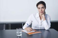 Σημειώσεις γραψίματος επιχειρηματιών στον πίνακα διασκέψεων Στοκ Φωτογραφία