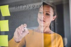 Σημειώσεις γραψίματος επιχειρησιακών γυναικών για τον πίνακα γυαλιού Στοκ εικόνες με δικαίωμα ελεύθερης χρήσης