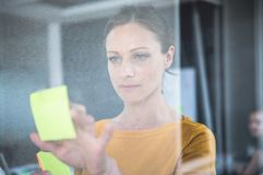 Σημειώσεις γραψίματος επιχειρησιακών γυναικών για τον πίνακα γυαλιού Στοκ φωτογραφία με δικαίωμα ελεύθερης χρήσης
