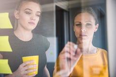Σημειώσεις γραψίματος επιχειρησιακών γυναικών για τον πίνακα γυαλιού Στοκ Εικόνα