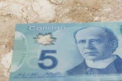 Σημειώσεις εγγράφου από τον Καναδά δολάριο Κινηματογράφηση σε πρώτο πλάνο στο μαρμάρινο πίνακα