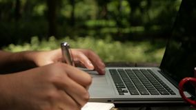 Σημειώσεις ενός ατόμων γραψίματος για το ξύλινο γραφείο στο πράσινο πάρκο απόθεμα βίντεο