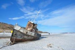 Σιβηρία, λίμνη Baikal, νησί Olkhon, ακρωτήριο Khoboy, Ρωσία, 11 Μαρτίου, 2017 Παλαιό σκουριασμένο σκάφος στην άκρη του επίσημου δ στοκ φωτογραφίες