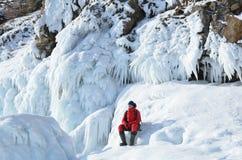 Σιβηρία, λίμνη Baikal, νησί Olkhon, ακρωτήριο Khoboy, Ρωσία, 22 Φεβρουαρίου, 2017 Ο τουρίστας κάθεται στη συγκέντρωση πάγου στην  στοκ φωτογραφία με δικαίωμα ελεύθερης χρήσης