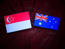 Σιγκαπούριος σημαία με την αυστραλιανή σημαία σε ένα κολόβωμα δέντρων Στοκ Φωτογραφία