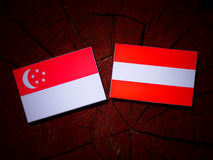 Σιγκαπούριος σημαία με την αυστριακή σημαία σε ένα κολόβωμα δέντρων Στοκ Φωτογραφία