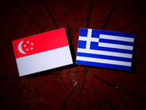 Σιγκαπούριος σημαία με την ελληνική σημαία σε ένα κολόβωμα δέντρων που απομονώνεται Στοκ Εικόνες
