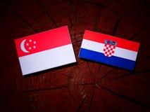 Σιγκαπούριος σημαία με την κροατική σημαία σε ένα κολόβωμα δέντρων Στοκ Εικόνες