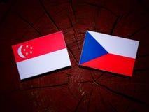 Σιγκαπούριος σημαία με την τσεχική σημαία σε ένα κολόβωμα δέντρων που απομονώνεται Στοκ Εικόνες