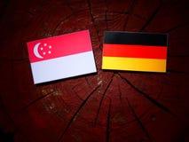 Σιγκαπούριος σημαία με τη γερμανική σημαία σε ένα κολόβωμα δέντρων Στοκ φωτογραφία με δικαίωμα ελεύθερης χρήσης