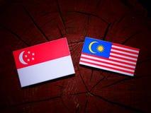 Σιγκαπούριος σημαία με τη μαλαισιανή σημαία σε ένα κολόβωμα δέντρων που απομονώνεται Στοκ φωτογραφία με δικαίωμα ελεύθερης χρήσης
