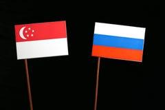 Σιγκαπούριος σημαία με τη ρωσική σημαία στο Μαύρο Στοκ Εικόνες