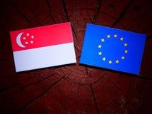 Σιγκαπούριος σημαία με τη σημαία της ΕΕ σε ένα κολόβωμα δέντρων που απομονώνεται Στοκ φωτογραφία με δικαίωμα ελεύθερης χρήσης