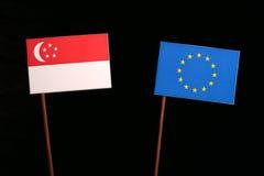 Σιγκαπούριος σημαία με τη σημαία της ΕΕ της Ευρωπαϊκής Ένωσης στο Μαύρο Στοκ φωτογραφία με δικαίωμα ελεύθερης χρήσης