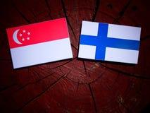 Σιγκαπούριος σημαία με τη φινλανδική σημαία σε ένα κολόβωμα δέντρων που απομονώνεται Στοκ Εικόνα