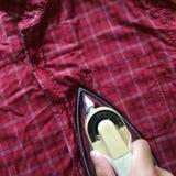 Σιδέρωμα ενός κόκκινου ελεγμένου πουκάμισου στοκ φωτογραφία