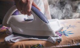 Σιδερώνοντας τα ενδύματα στο σιδέρωμα του πίνακα Στοκ Εικόνες